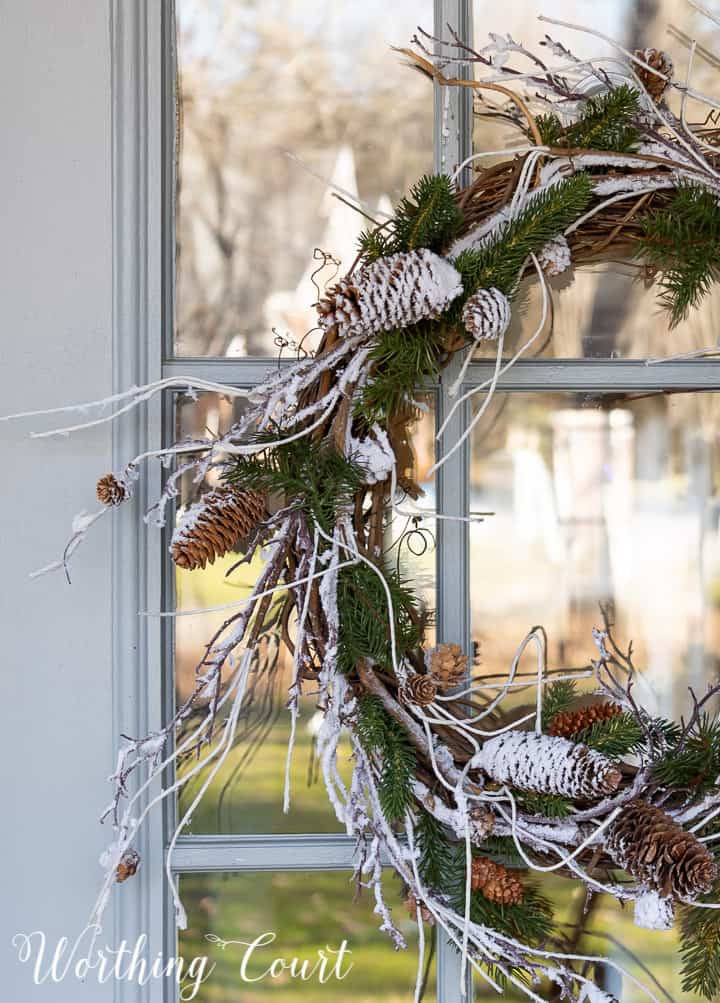 winter wreath with snow and pine branches and pinecones with a bow hanging on a glass door