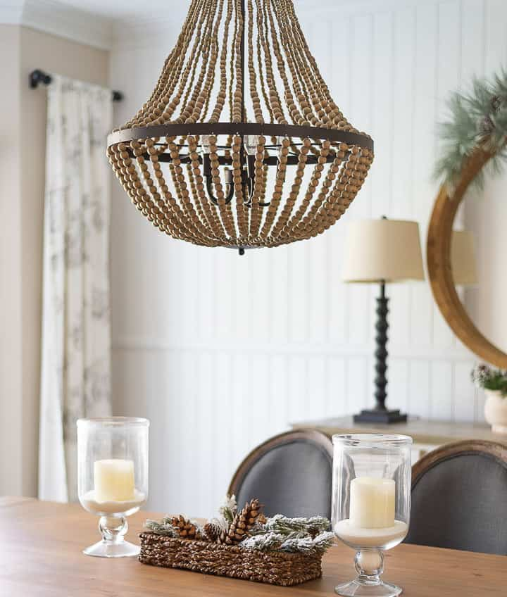 beaded chandelier above dining room table with a pair of glass lanterns for the centerpiece
