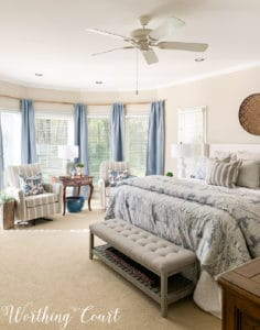 bay window with blue curtains, two side chairs and a king size bed with blue, white and gray bedding in a master bedroom