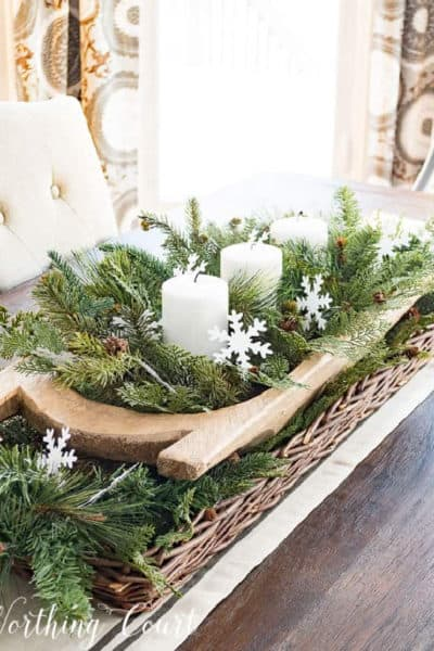 wood dough bowl nestled inside a long wicker basket filled with faux greenery, paper snowflakes and white candles