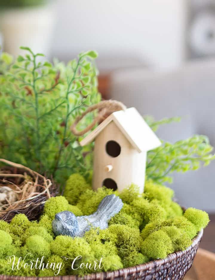 wicker bowl filled with green moss, faux greenery, a nest and faux bird