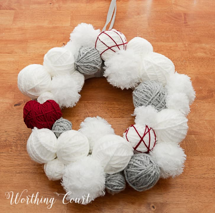 Valentine's Day wreath made with styrofoam balls covered with white and gray yarn and a heart cutout wrapped with red yarn