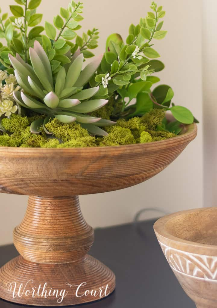 wooden pedestal bowl filled with green moss and faux succulents