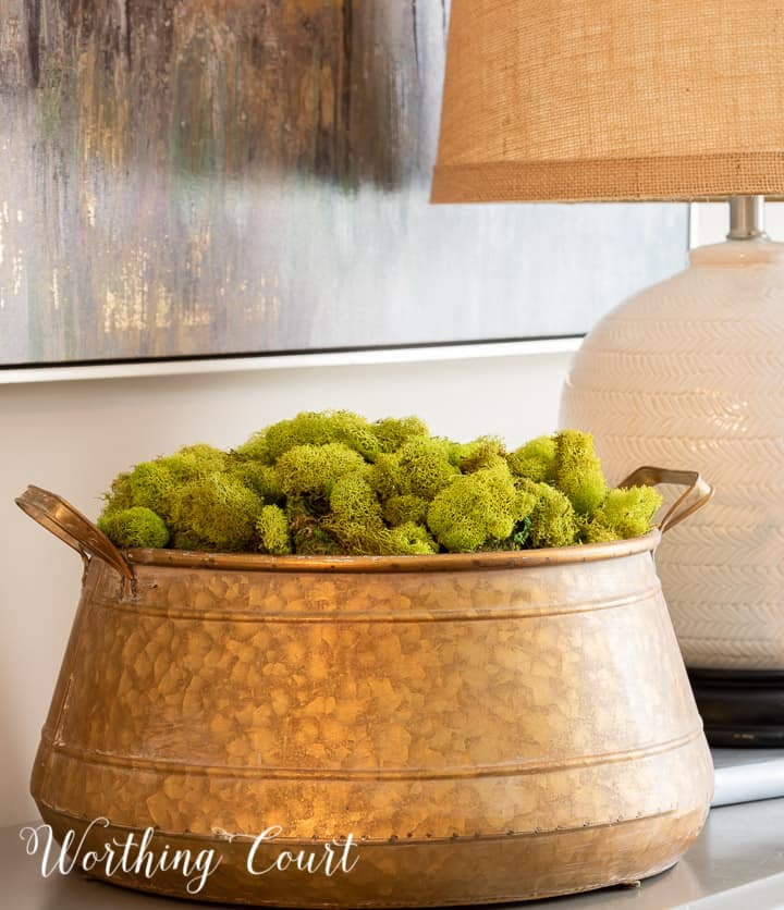 brass bowl filled with green moss on a small chest