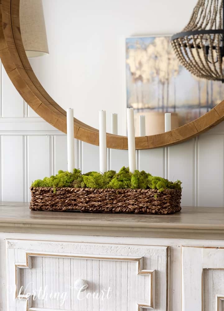 rectangular wicker basket with low sides filled with green moss and 3 tapered white candles on a sideboard