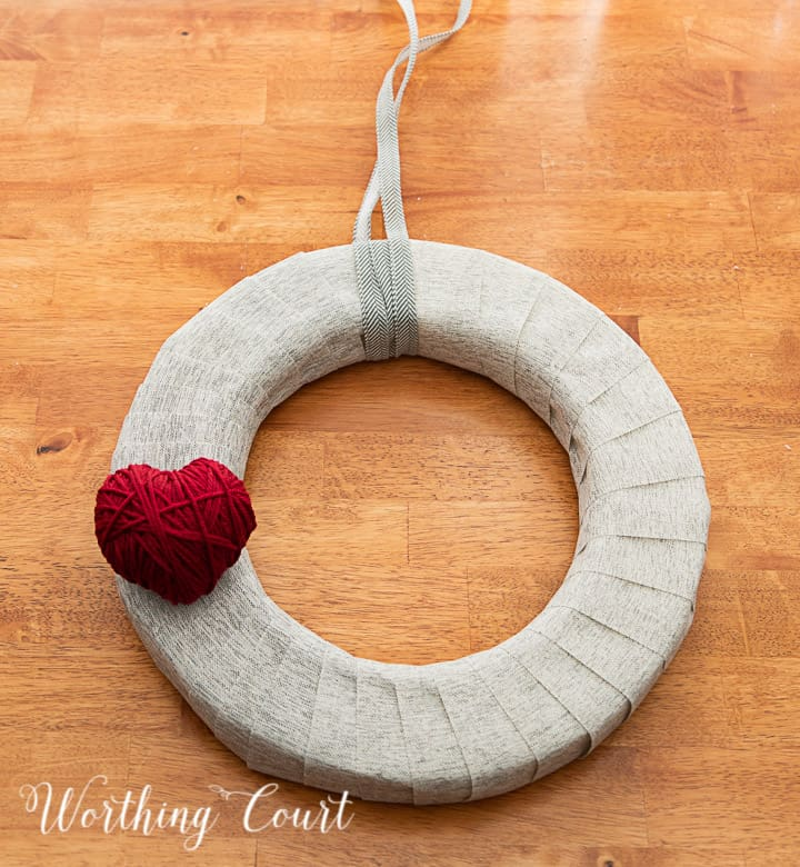 In process photo of tutorial about how to make a Valentine's Day wreath with yarn balls