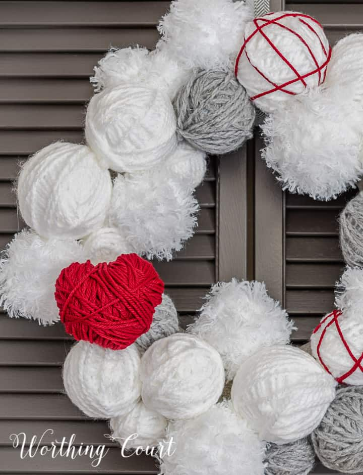 Partial view of Valentine's Day wreath made with styrofoam balls covered with white and gray yarn and a heart cutout wrapped with red yarn