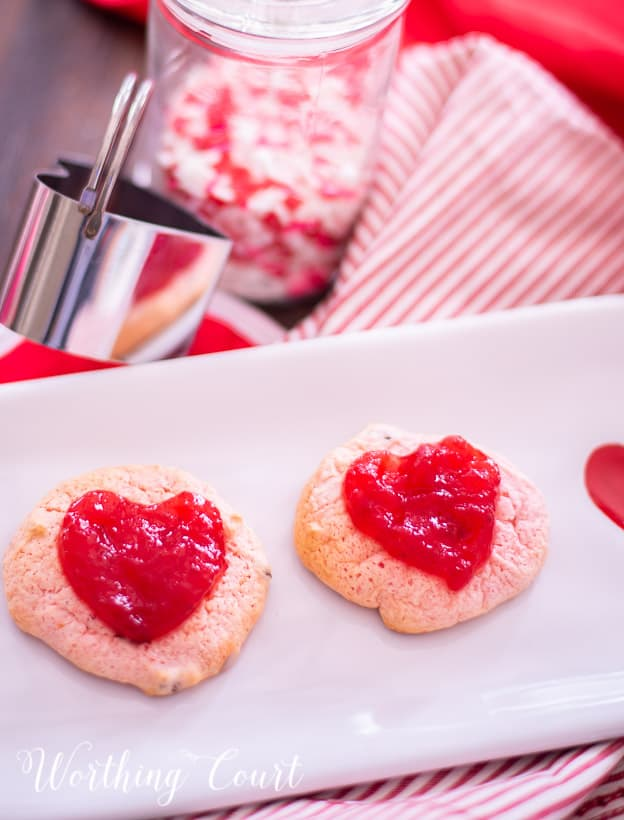 strawberry cookies on a white plate staged with other red and white items for Valentine's Day
