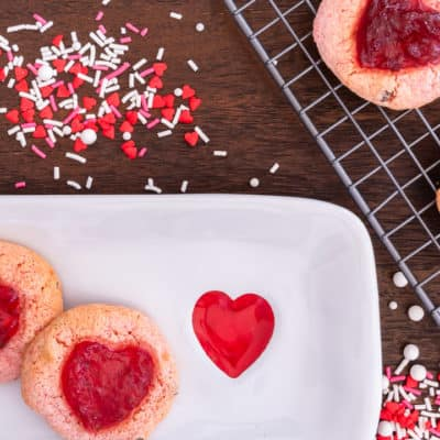 strawberry cookies on a white plate surrounded with red, white and pink sprinkles