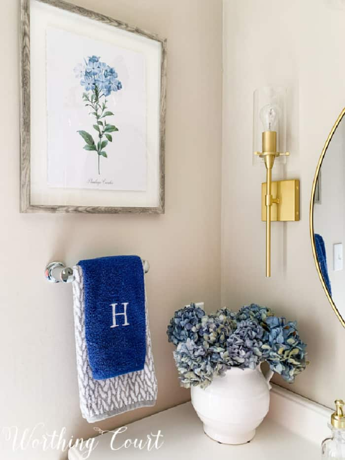 blue hydrangeas in a vase in a bathroom corner