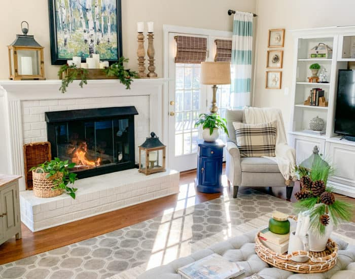family room with white fireplace and gray recliner in corner with art and accessories