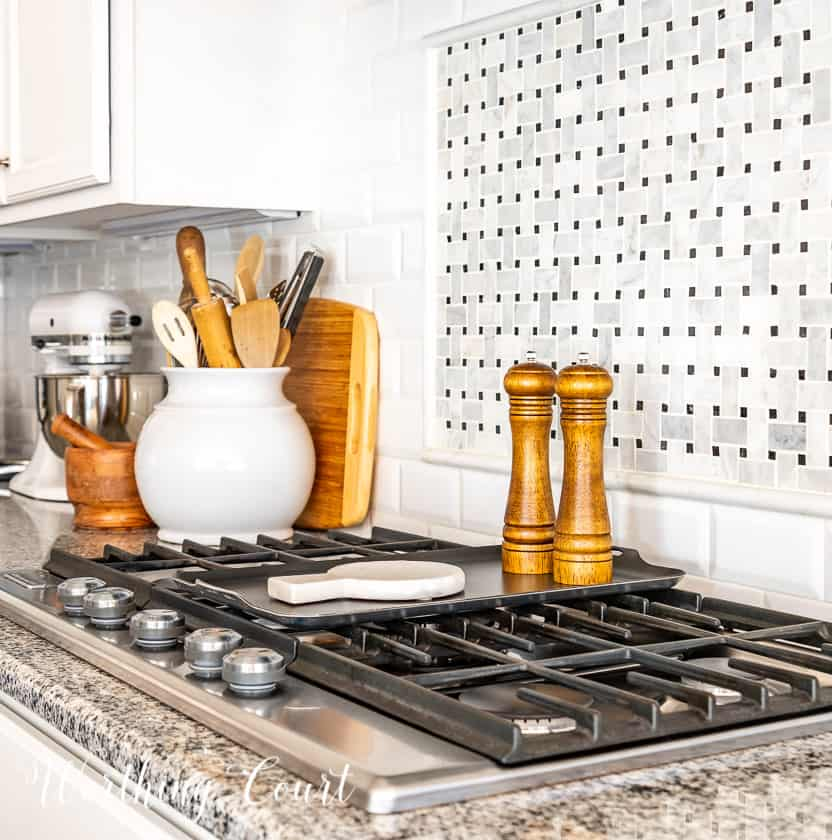 wood salt and pepper mill and marble spoon rest on top of burner griddle and other decorative items on countertop