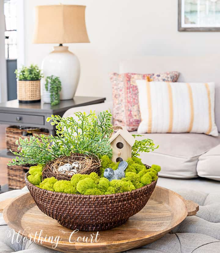 spring coffee table arrangement in a wicker bowl with moss, birdhouse, nest and greenery with couch in the background