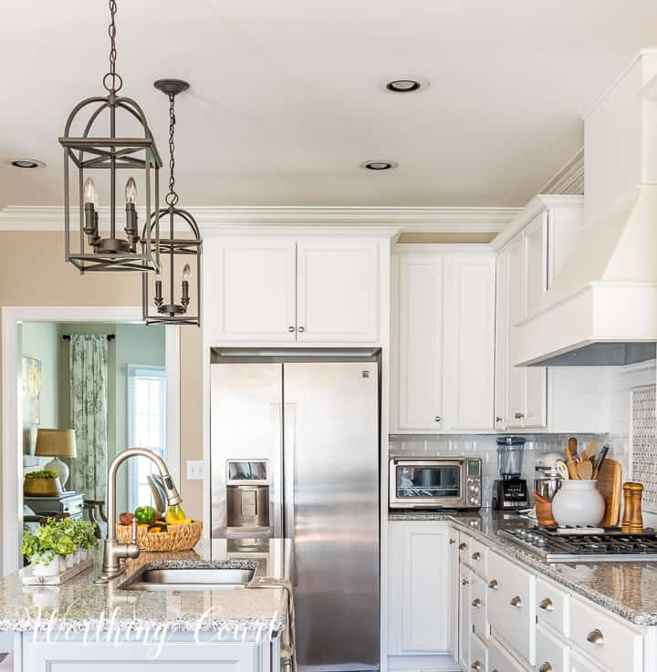 end view of kitchen with white cabinets and gray island