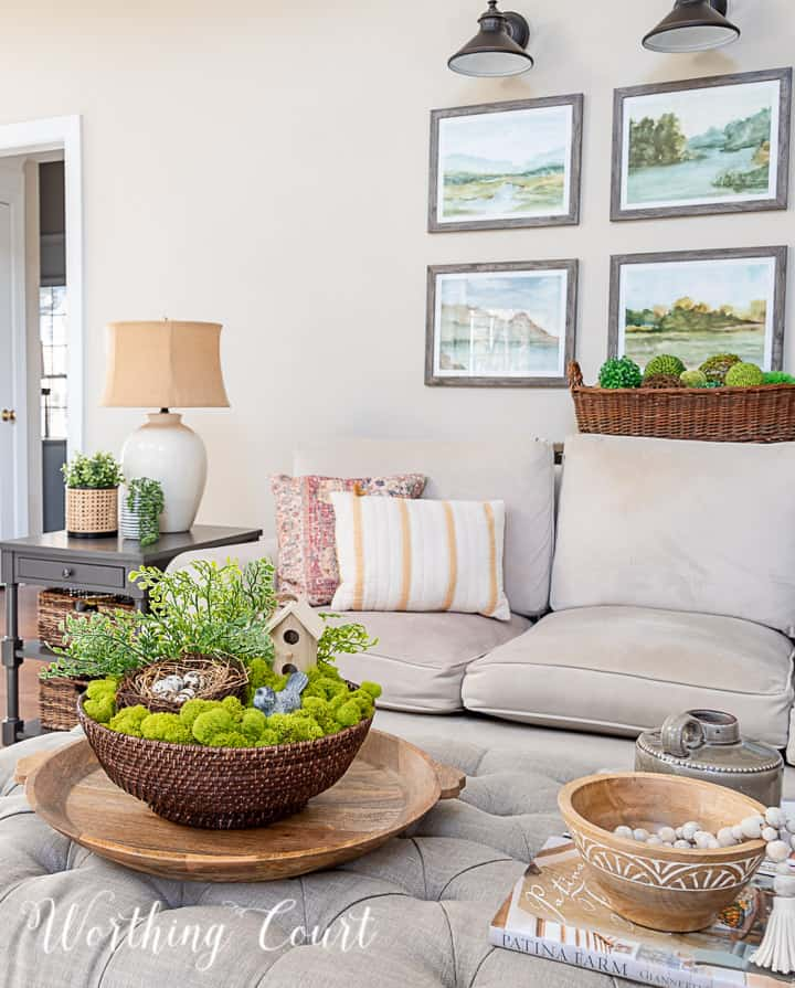 upholstered coffee table with spring decor and a gray couch with spring pillows in the background