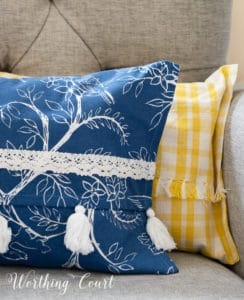portion of a blue and white and yellow and white pillow in a gray chair