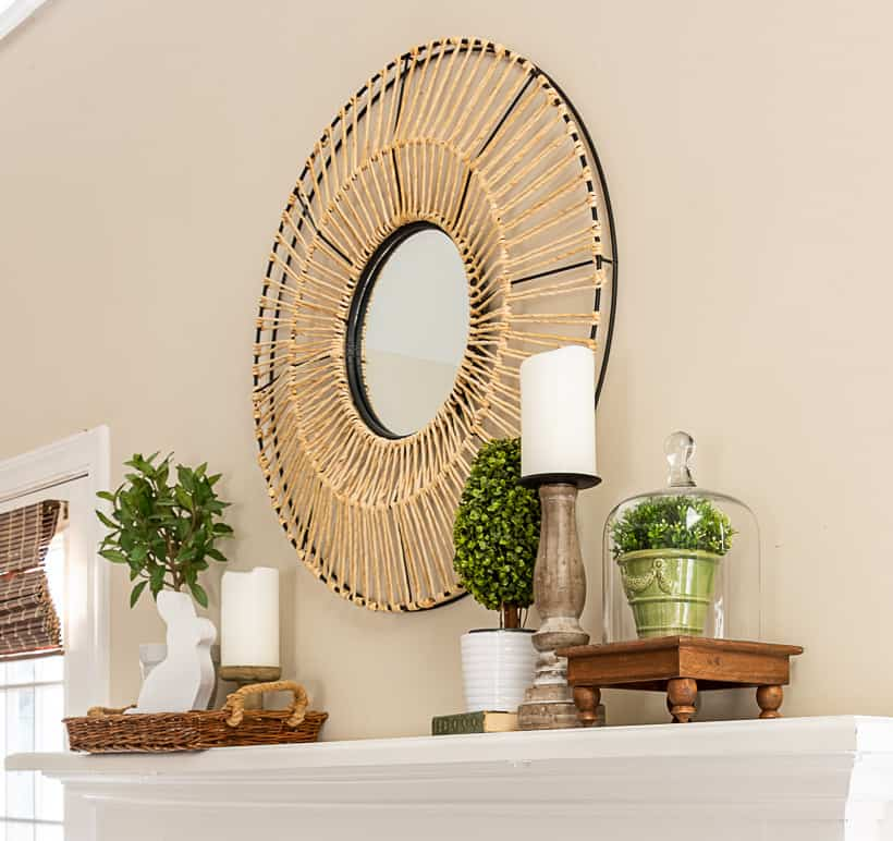 fireplace mantle with a round mirror above and spring decorations on each end