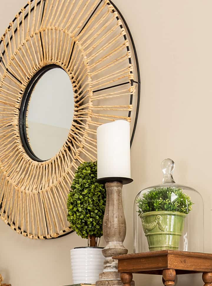 spring vignette with a topiary, candle and small plant under a glass cloche with a round mirror in the background