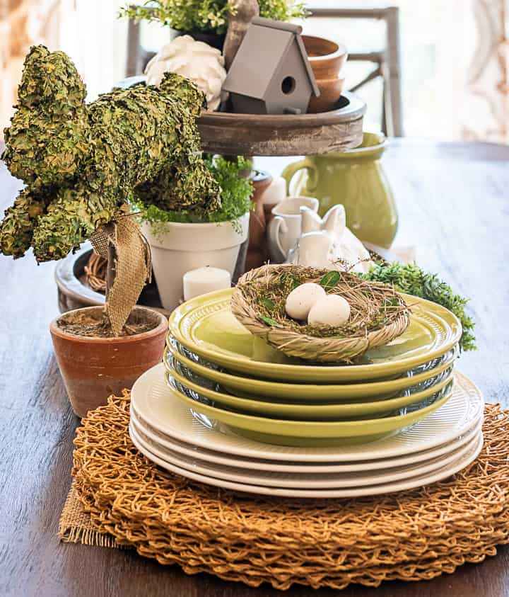 portion of a spring centerpiece with stacked green and white plates and a bunny topiary