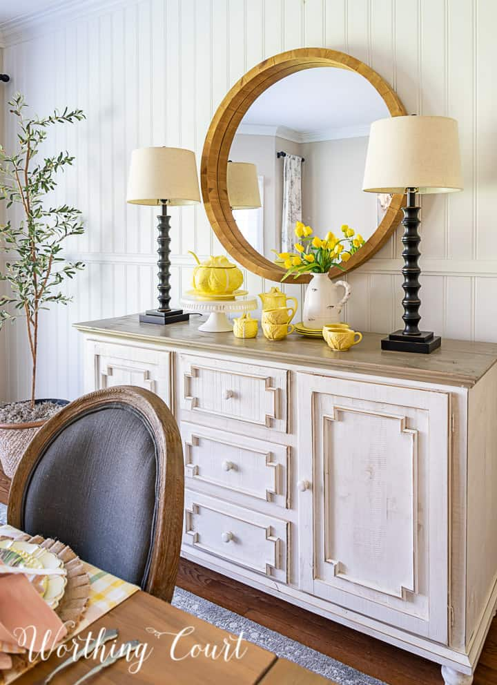 white sideboard with lamps and a round mirror above styled with yellow dishes for Easter