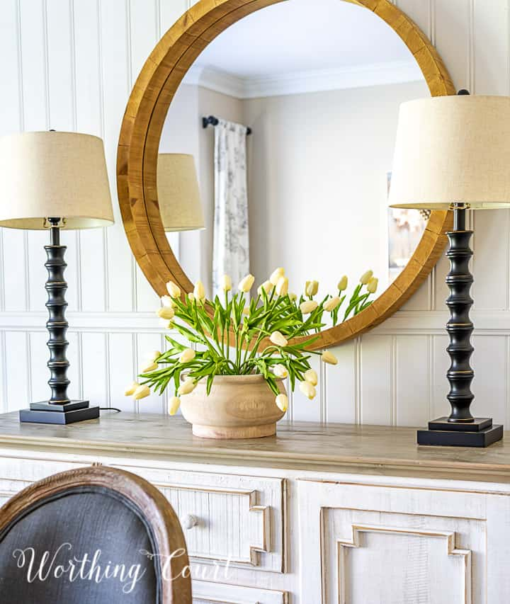 side board with round mirror above, two buffet lamps and white tulips in a wood bowl