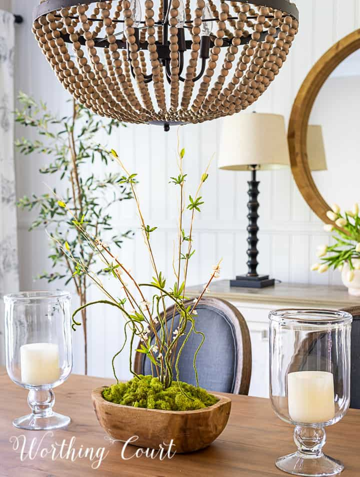 neutral dining room table with gray side chairs and white sideboard with spring decor