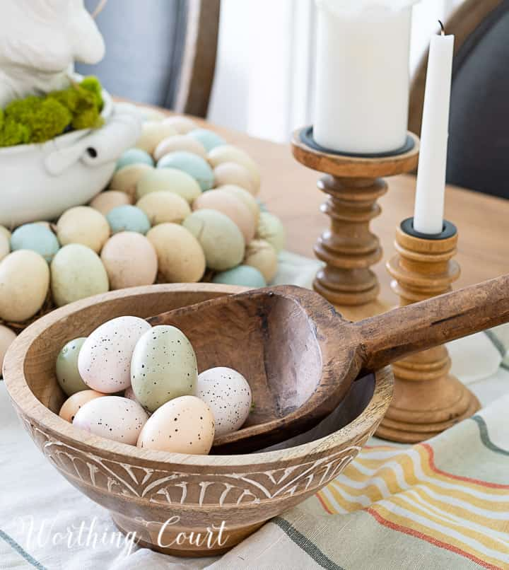 Partial view of Easter centerpiece with white ceramic bunny in the middle of an egg wreath and a wood bowl filled with faux Easter eggs