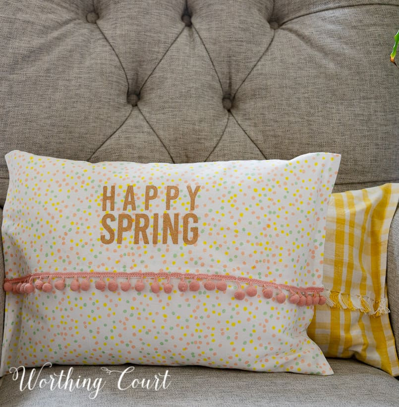 yellow and white and multi colored dots pillows in a gray chair