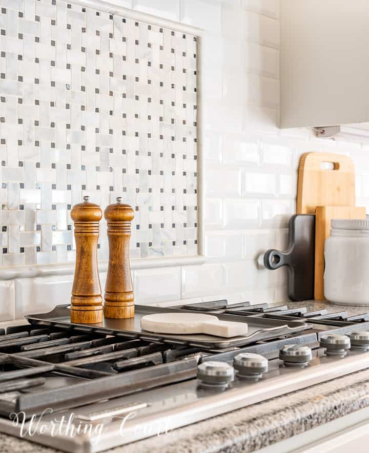 wood salt and pepper mill and marble spoon rest on top of burner griddle