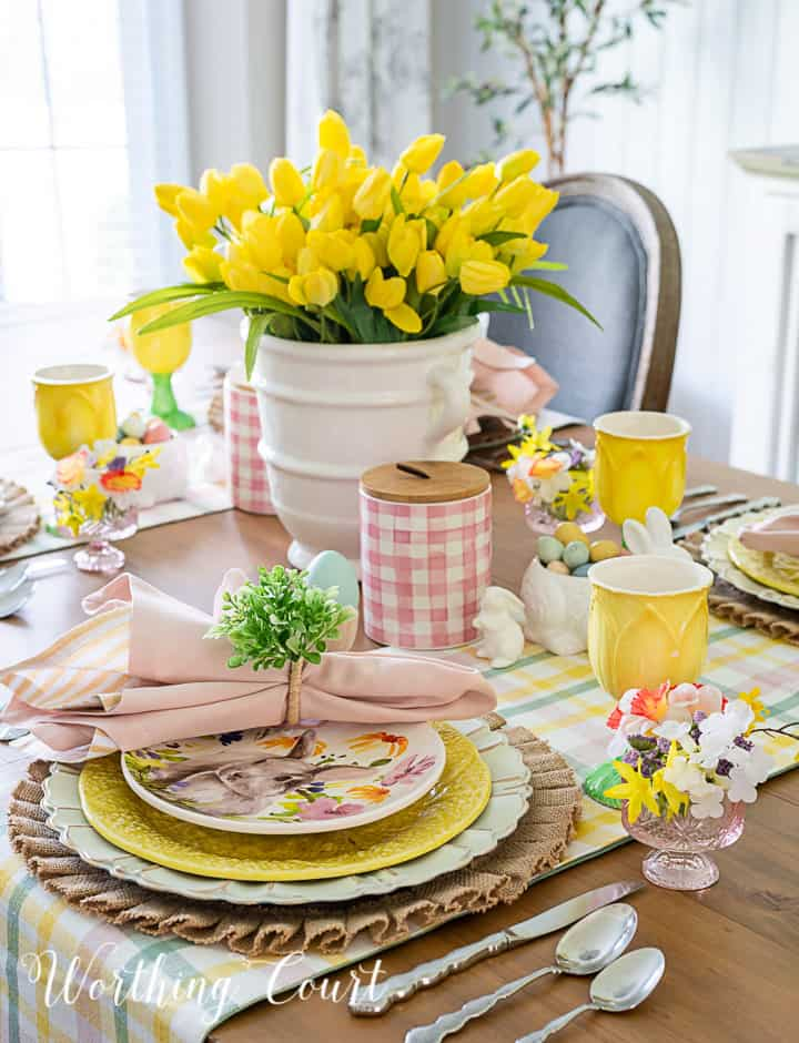 Portion of an Easter tablescape using yellow dishes and faux flowers