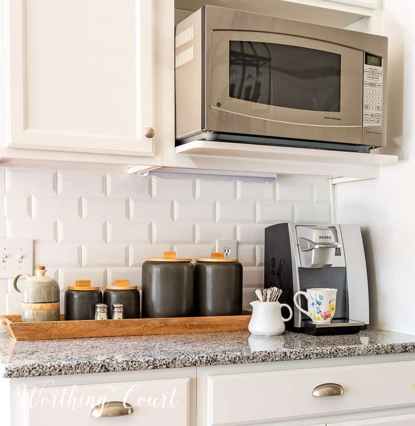 gray canisters and coffee maker in a kitchen with white cabinets and subway tile backsplash
