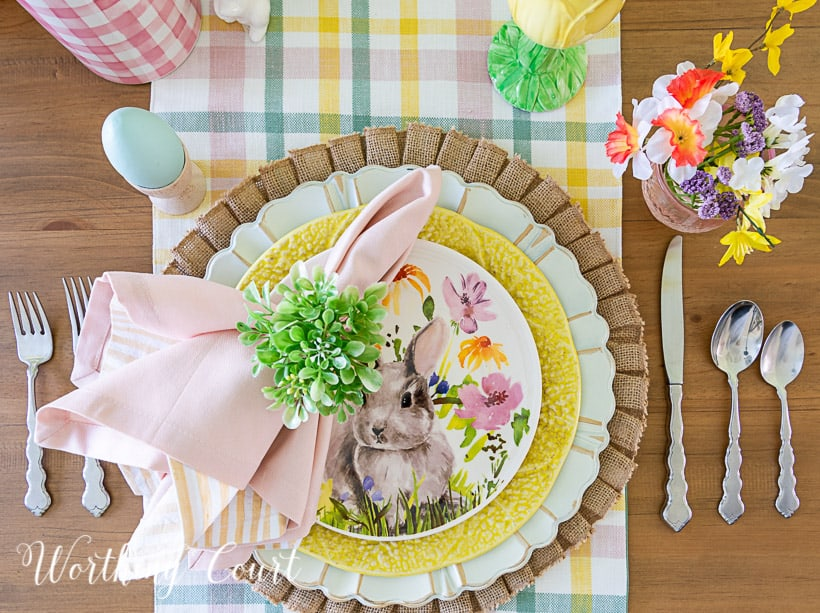 Easter place setting with burlap placemat topped with a charger, yellow plate and bunny salad plate