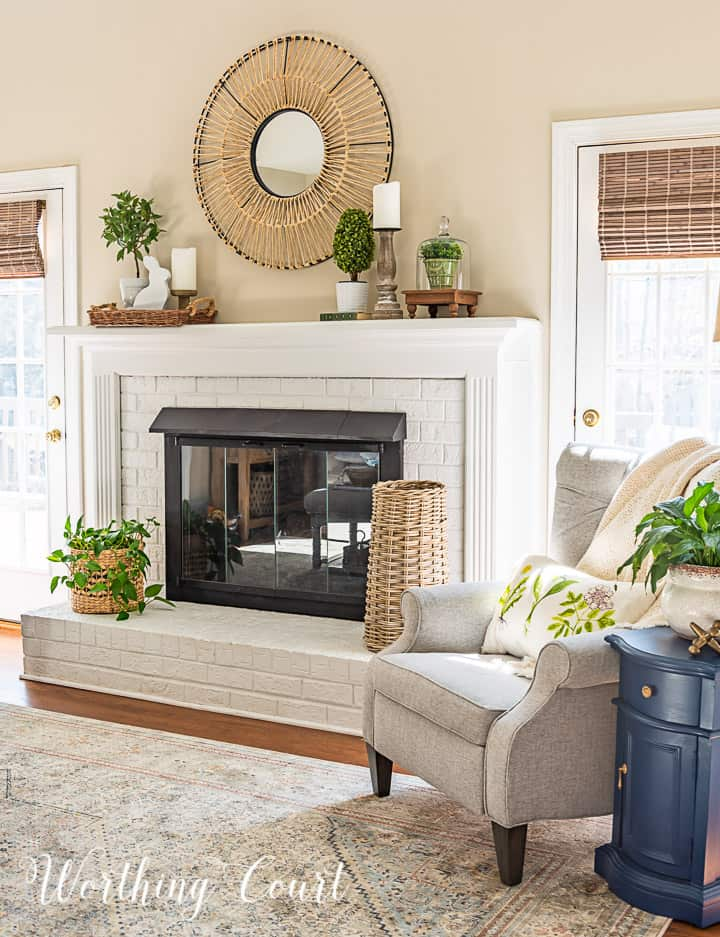 gray chair beside white fireplace with spring decorations on the mantle