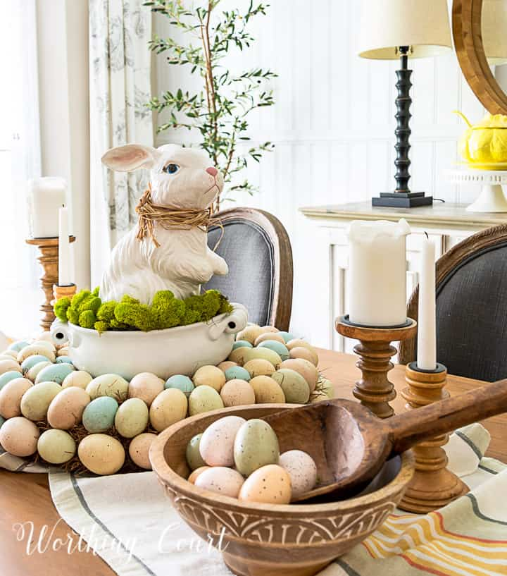 Easter centerpiece with white ceramic bunny in the middle of an egg wreath and a wood bowl filled with faux Easter eggs