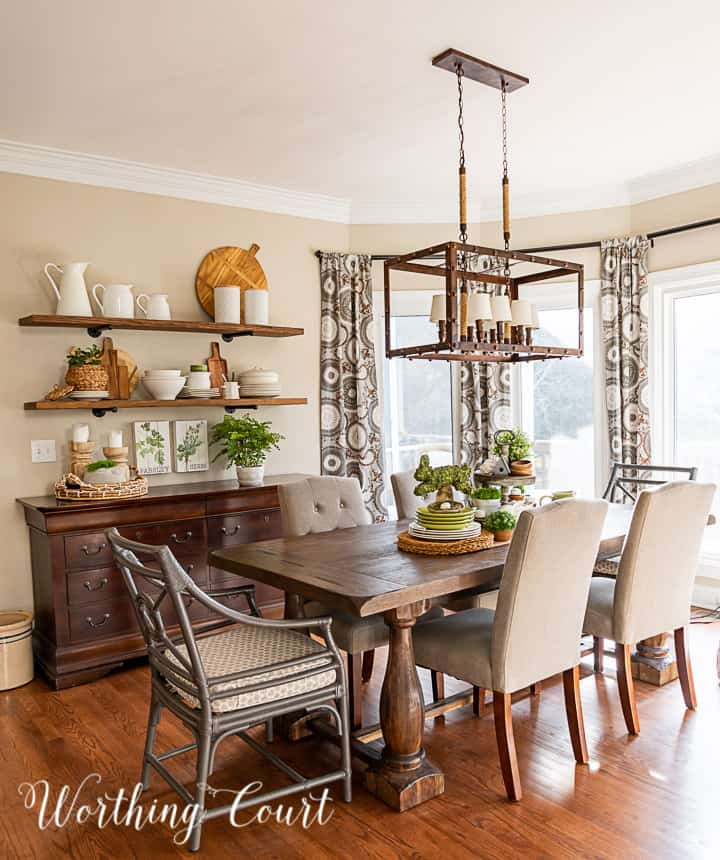 breakfast room with open wall shelves over a sideboard and spring decorations