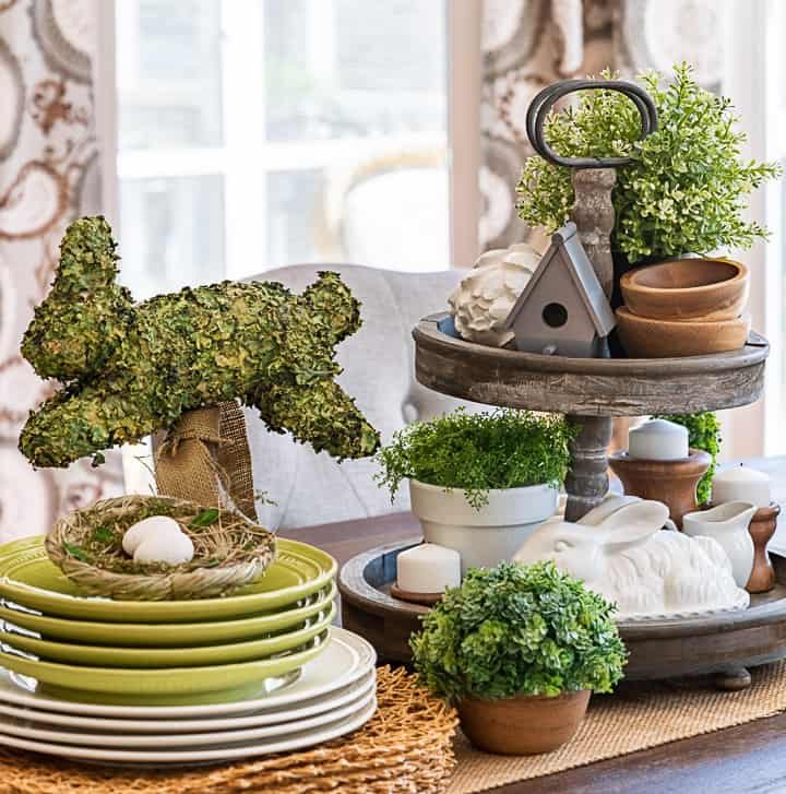 tiered tray decorated for spring with greenery, a birdhouse, candles and a bunny beside stacked plates and a bunny topiary