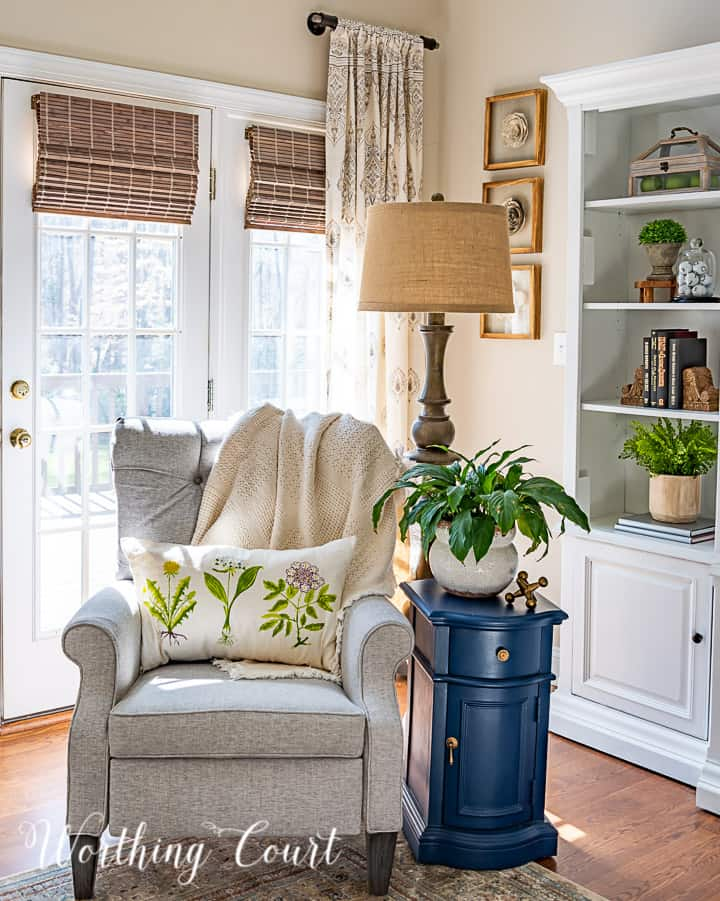 gray chair with tufted back with a floor lamp and blue side table with a spring pillow and live plant