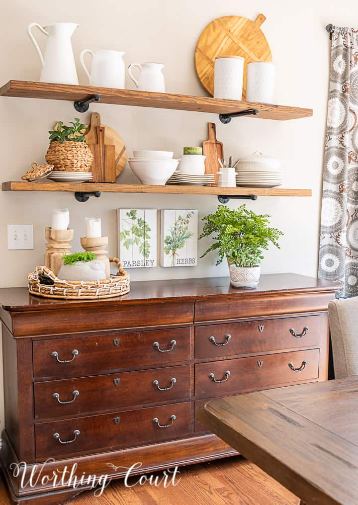 open wood shelves decorated with white dishes, greenery and light wood toned accessories