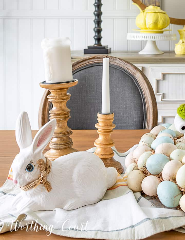 White ceramic bunny and wood candlesticks with white candles in an Easter centerpiece