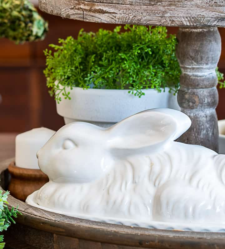 bottom level of a tiered tray with a white bunny and faux greenery