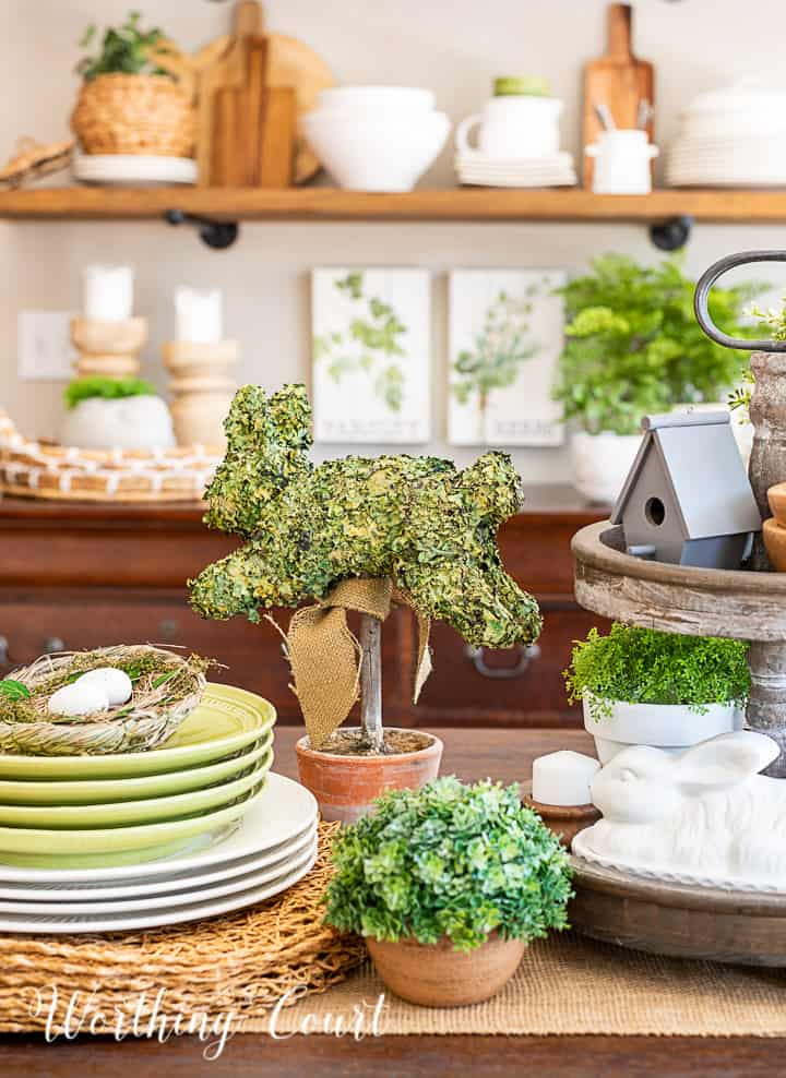 portion of a spring centerpiece with bunnies, greenery and white accessories and dishes