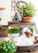 tiered tray decorated for spring with greenery, a birdhouse, candles and a bunny