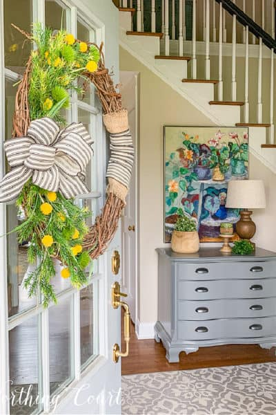 view of spring decor looking through a front door with a wreath hanging on it