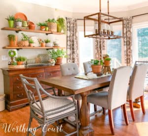 dining area with table, sideboard, open shelves and terra cotta decor