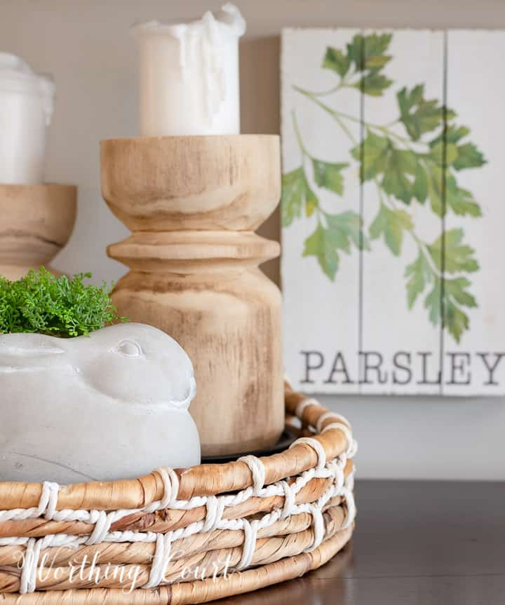 vignette with wood candlesticks and a concrete bunny in a round basket tray