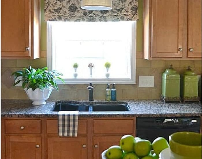 window and cabinets in a kitchen with green walls