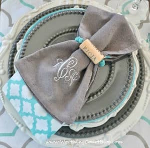stack of gray and white plates topped with gray, white and blue napkins and a diy wine cork napkin ring