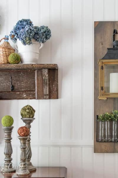 lantern and vintage shelf with farmhouse style accessories hanging on a white wall