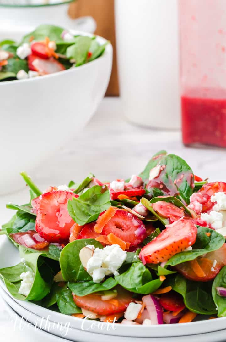 strawberry spinach salad in white bowls
