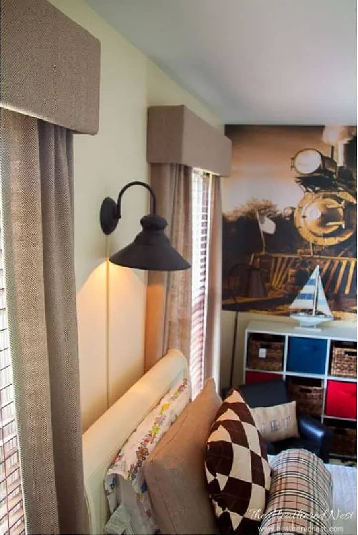 pair of tan draperies with cornices with sconce between